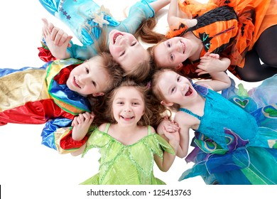 Four laughing girls and one boy, dressed in fancy dress, lie on floor head-to-head in form of flower petal