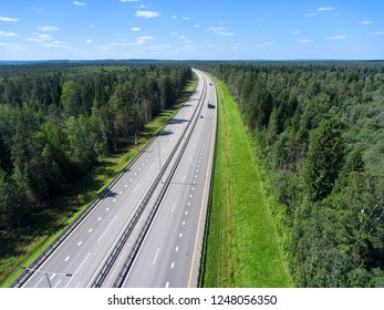 Four lines wide highway passing in green forest, vehicle driving on lane, aerial view