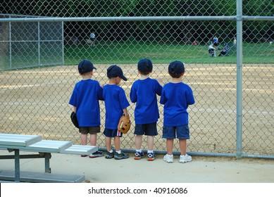 four little boys wait for their baseball game to begin