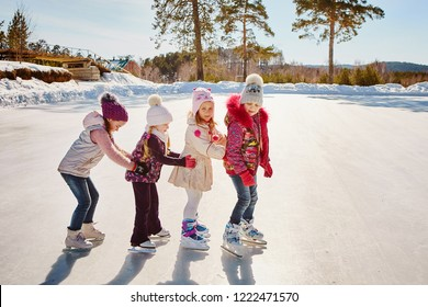 Four little happy girls are skating. They have fun with friends.