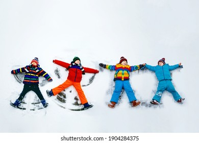 Four little kid boys in colorful winter clothes making snow angel, laying down on snow. Active outdoors leisure with children in winter. Happy friends with warm hat, gloves, winter fashion