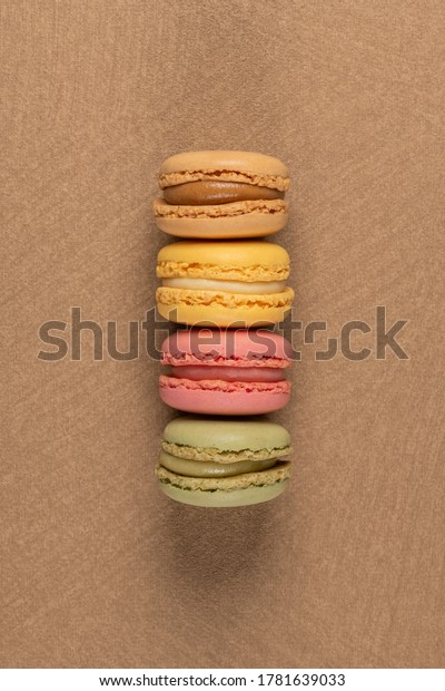 Four macaroons on brown vinyl background.