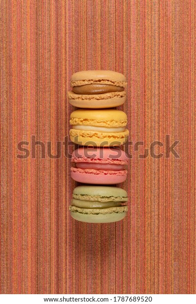 Four macaroonson red vinyl background.