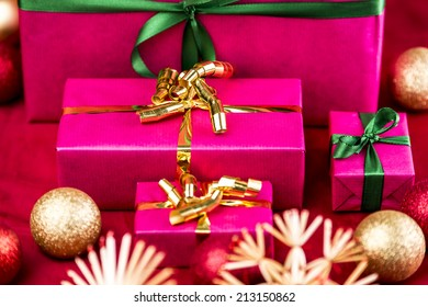 Four magenta gifts ready for handing out of presents. Surrounded by blurred Christmas bulbs and straw stars on a red cloth. Narrow depth of field runs across the golden bow of the medium-sized box.