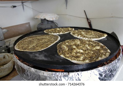 Four manaqeesh being baked on a saj oven, the mankousheh is a famous Lebanese breakfast.
