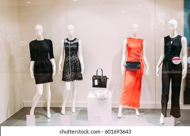 Four Mannequins Standing In Store Window Display Of Women's Casual Clothing Shop In Shopping Mall.