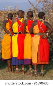 Four Masai Mara women preparing to dance