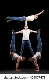 four men doing acrobatics trick in jeans at black background