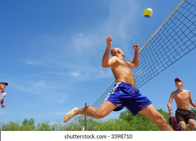 Four men playing beach volleyball - balding man runs after ball. Shot near Dnieper, Ukraine.