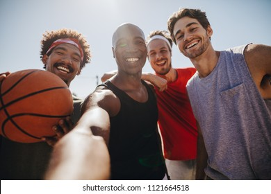 Four men posing for selfie holding a basketball. Smiling athletes enjoying while playing basketball.