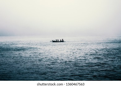 Four men in a small fishing boat rowing on a lake, foggy weather without good sight, rain drops on water