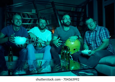 Four men watching american football on TV, they are cheering while sitting on sofa