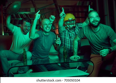 Four men watching american football on television, dark room, light coming only from TV