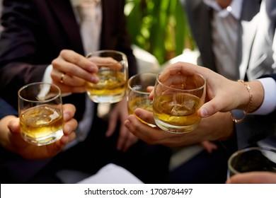 Four men's hands holding glasses of whiskey on the rocks.