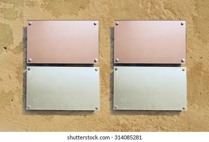 Four metal information boards on a terracotta wall