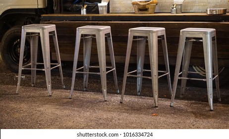 Four metal stools/chairs on the gravel road, beside the food truck with wooden bar, ready for sitting and order some food or drinks in the night
