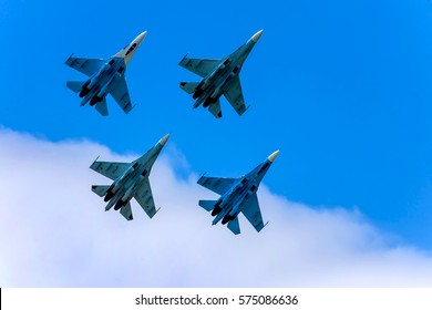 Four military aircrafts flying together in the sky during airshow