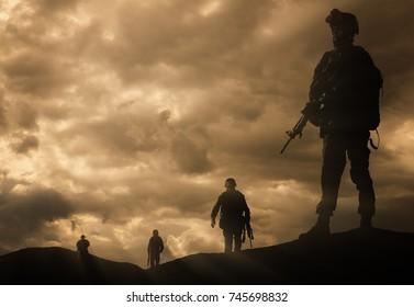 Four military silhouettes on sunset sky background