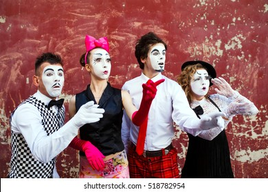 Four mimes looking aside on the background of a red wall.