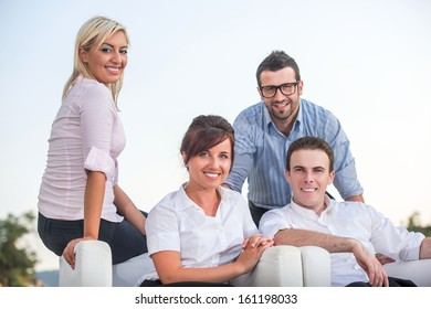 Four modern looking people posing outside