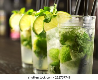 Four Mojito cocktails on a bar counter