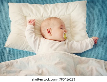 Four month old baby sleeping on blue blanket