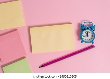 Four multicolor blank notepads message marker pen small alarm clock wakeup colored background empty text important events home office school house everywhere