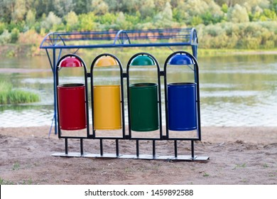 four multi-colored garbage containers stand on the beach by the river near the forest