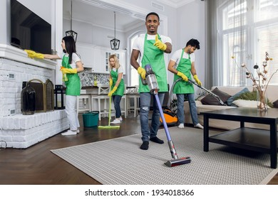 Four multicultural janitors in green apron and yellow rubber gloves wiping furniture, vacuuming carpet and washing floor. Concept of cleaning industry.