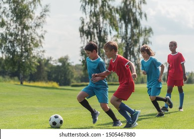 four multicultural kids playing football on grass