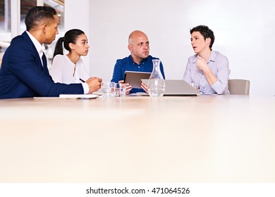 four multiethnic business partners busy negotiating the terms of their future business together as a team in a collaborative effort.