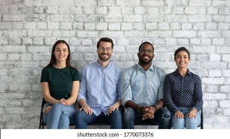 Four multiethnic competitive applicants sit on chairs wait turn for job interview. Skilled candidates with higher education and good chance of acceptance. HR new company employees and interns portrait
