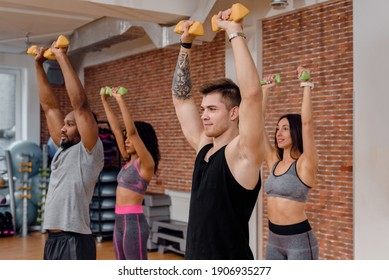 Four multiethnic strong athletic friends doing weight lifting exercise