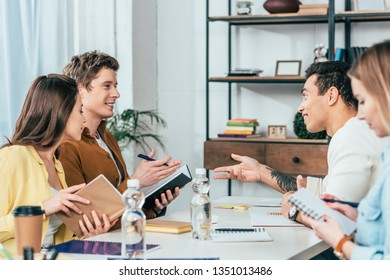 Four multiethnic students with notebooks and books discussing with smile at table
