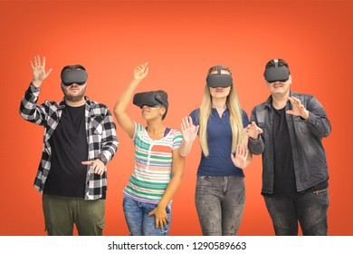 Four multiracial friends playing vr glasses isolated living on coral background. Virtual reality concept with young people having fun together connecting with headset goggles. Digital generation trend