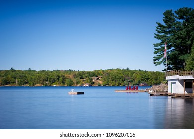 Four Muskoka chairs sitting on a wood dock facing a lake. Across the calm water are cottages nestled among green trees. The Canadian flag is visible. There are no clouds in the sky.