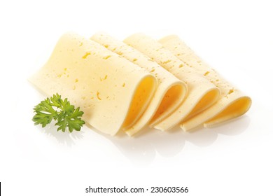Four neatly folded and displayed Swiss tilsit cheese slices garnished with a sprig of fresh parsley on a white background
