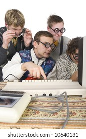 Four nerdy guys sitting in front of old-fashioned computer. One of them is pushing the button on keyboard. Side view, white background