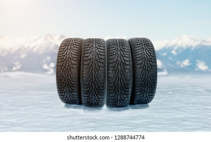 Four new winter tires on an icy surface as a symbol of safe driving during snowy season