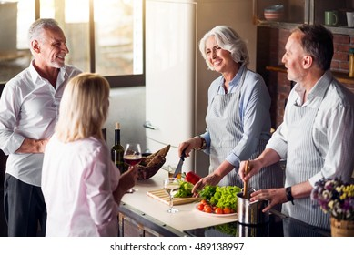 Four nice elderly people gathered around table in kitchen