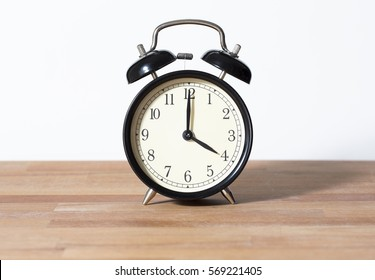 It is four o'clock. The time is 4:00 am or pm. A retro clock isolated on wooden table. White background. Copy space and cut.
