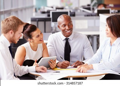 Four office colleagues in a casual team meeting