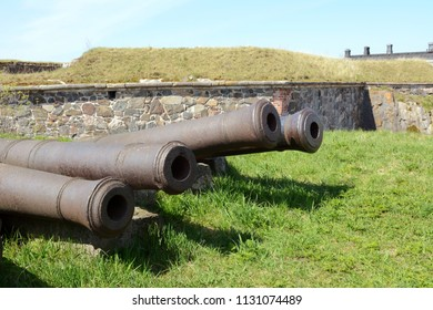 Four old abandoned military cannons on grass in a Suomenlinna bastion