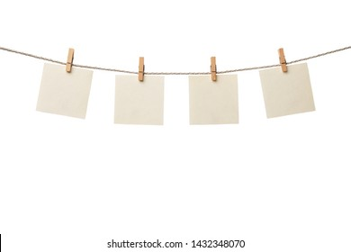 Four old paper blank notes hanging on the rope with wooden clothespins isolated on white background