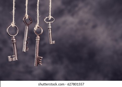 Four old rusty keys hanging on dark abstract background with copy space. Security concept
