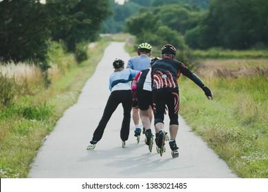 Four older people riding on roller skates in line