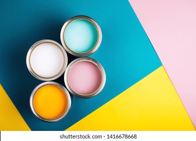 Four open cans on bright background. Yellow, white, pink, turquoise colors of paint. Top view. Renovation concept.