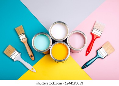 Four open cans of paint with brushes on bright background. Yellow, white, pink, turquoise colors of paint. Top view.