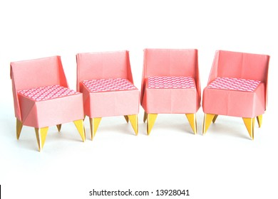 Four origami chairs on a white background