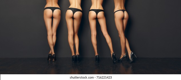 Four pairs of bare female legs leaning to the wall. Back side view.